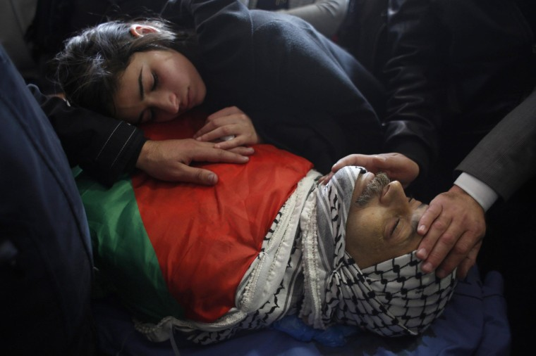 The daughter of Palestinian minister Ziad Abu Ein mourns over his body during his funeral in the West Bank city of Ramallah on Dec. 11, 2014.