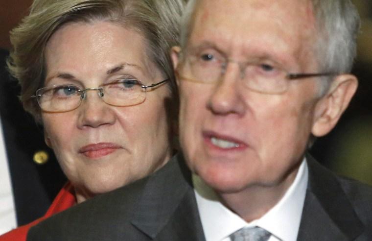 Image: U.S. Senator Warren stands behind Senate Majority Leader Reid after leadership elections for the Congress in Washington