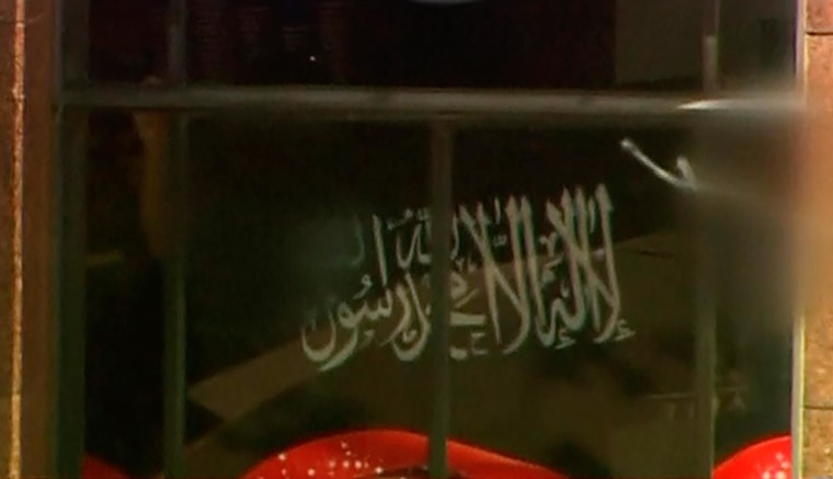Image: Video grab shows a black flag with white Arabic writing held up at the window of the Lindt cafe