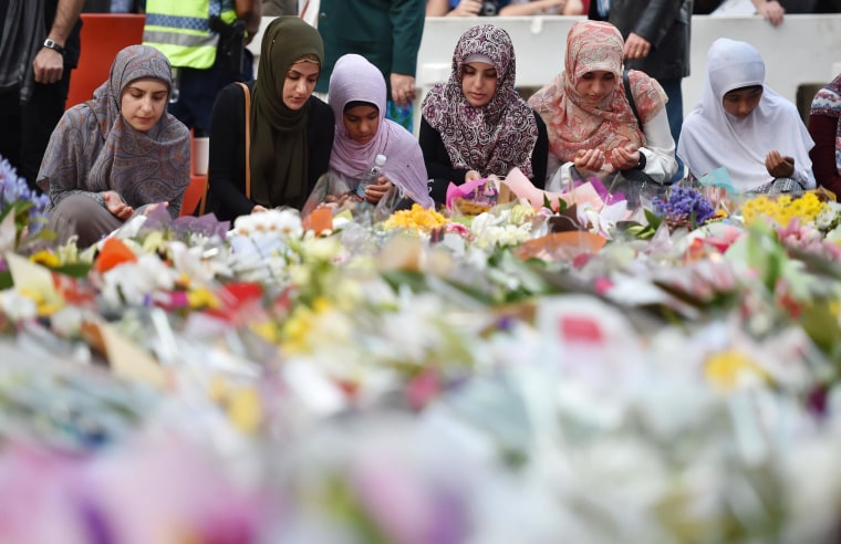 Image: Young Muslim women lay flowers at a makeshift memorial