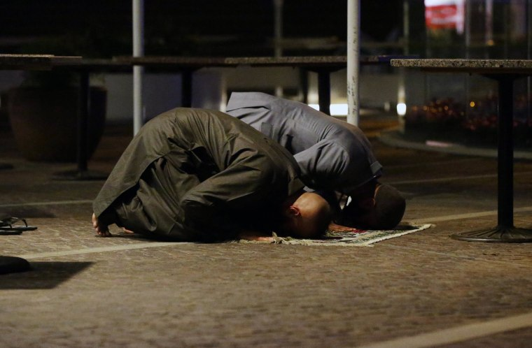 Image: Sam Tiger right, and Abdulrahman El-Lawn perform prayers