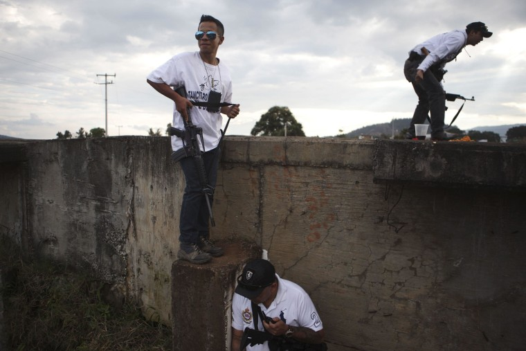 Image: Vigilantes stand guard next to a bridge during a blockade on a highway near the town of Uruapan in Michoacan state