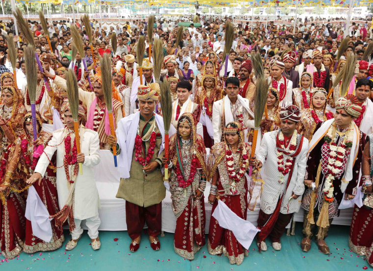 Image: Newly-married Hindu couples hold brooms as they pledge to clean their houses, after taking their wedding wows during a mass marriage ceremony in the western Indian city of Ahmedabad