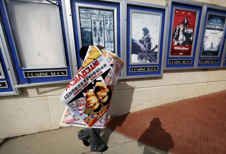 """A poster for the movie """"The Interview"""" is carried away by a worker after being pulled from a display case at a Carmike Cinemas movie theater, on Dec. 17, 2014 in Atlanta. Georgia-based Carmike Cinemas has decided to cancel its planned showings of """"The Interview"""" in the wake of threats against theatergoers by the Sony hackers."""