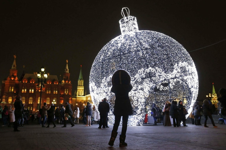 Image: A woman takes a picture near a giant Christmas ball as part of New Year and Christmas holiday season decorations in central Moscow