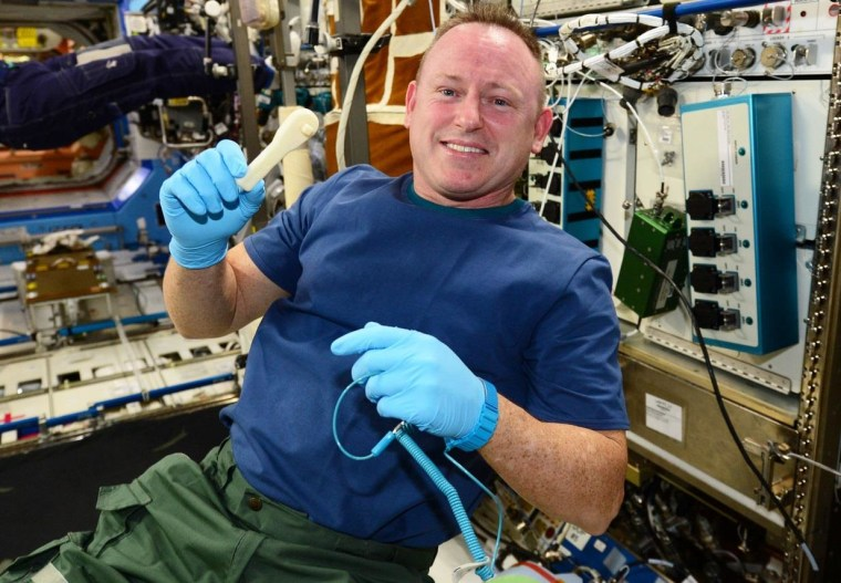 The International Space Station's commander, NASA Astronaut Barry Wilmore, shows off the 3-D-printed ratchet.