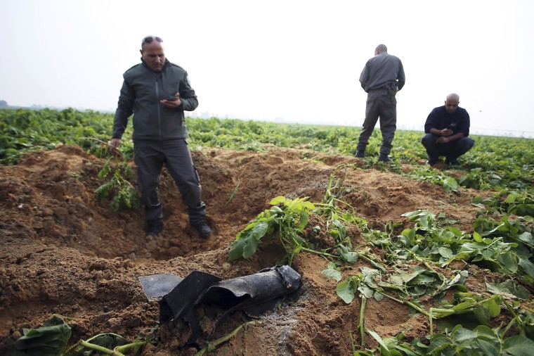 Israeli security forces stand next to the remains of a rocket that was fired from the Gaza Strip towards Israel on Friday, on the Israeli side of the border