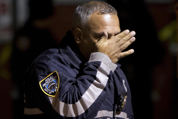 Image: A police officer wipes tears away from his face as he walks away from the scene of a shooting where two New York Police officers were shot dead in the Brooklyn borough of New York