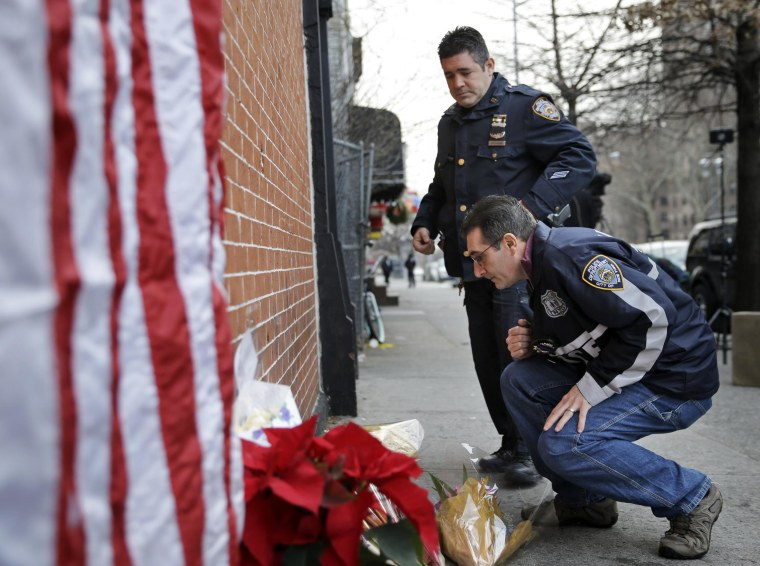 Image: Police officers leave candles at an impromptu memorial near the site where two New York City police officers were killed