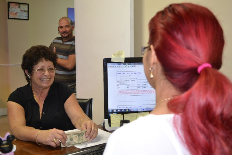 At Havana Centro Travel Agency a customer purchases a ticket for Cuba while another customer waits to be helped.