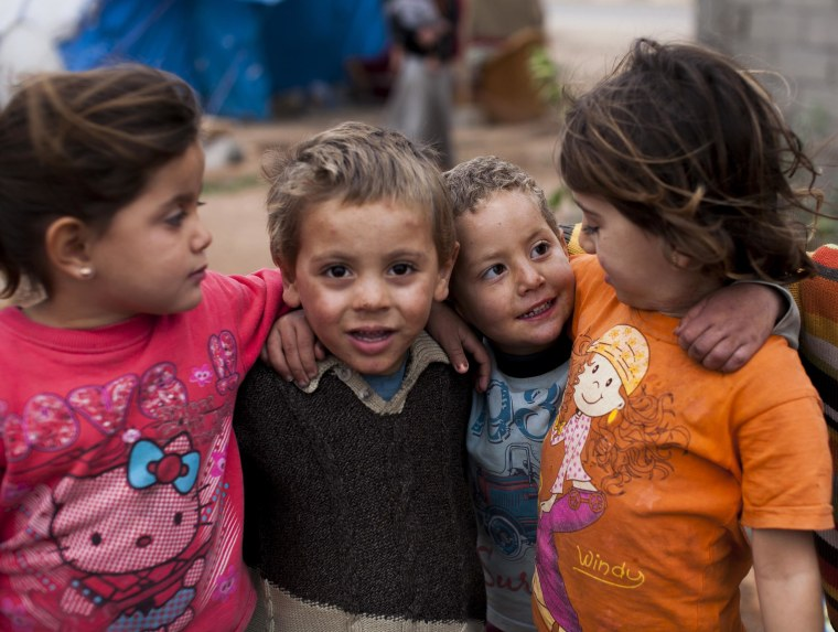 Murad, poses with friends, all Syrian refugees, near his family's tent , in Reyhanli, southern Turkey.