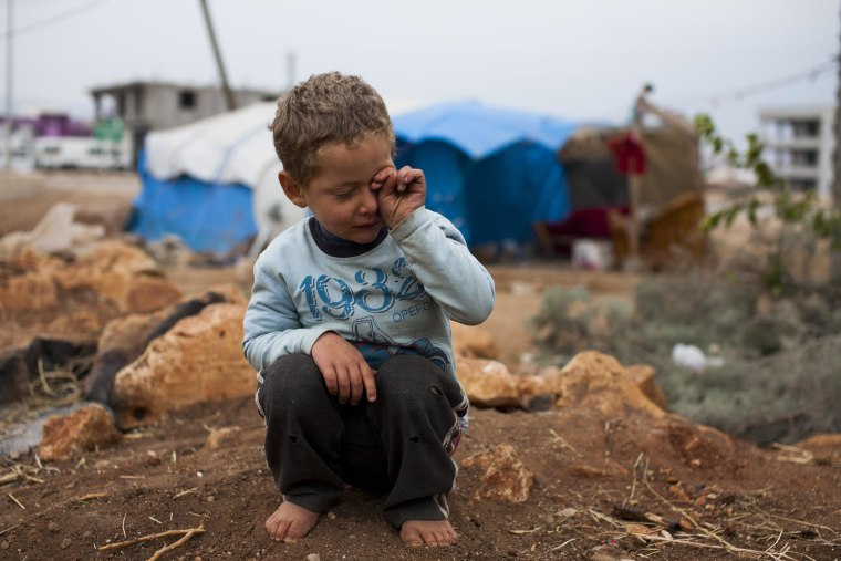 Murad tries to get sand from his eyes after playing with friends near his family's tent in Reyhanli, southern Turkey.