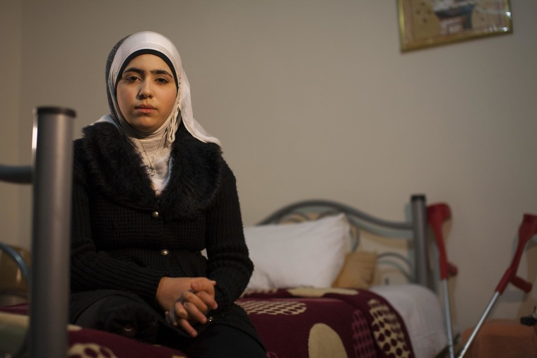 Noor sits in the hotel room she shares with her mother in Reyhanli, southern Turkey.