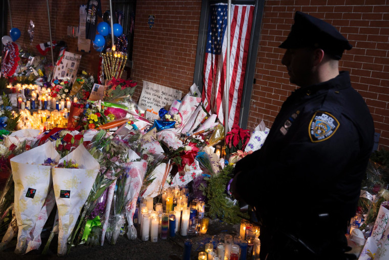 Image: An NYPD police officer stands guard beside a makeshift memorial