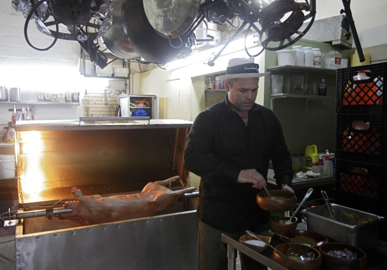 Image: Chef's Paella assistant chef Andres Roig prepares a pig at the company's kitchen in Miami, Florida
