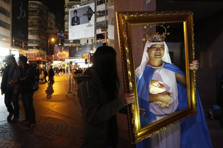 A man dressed as the Virgin Mary with baby Jesus poses for photographs during the early hours of Christmas Day celebrations in the Causeway Bay shopping district in Hong Kong on Dec. 25.