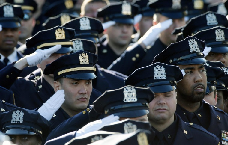 Image: Police salute during the playing of the U.S. National Anthem outside the Christ Tabernacle Church at the start of the funeral service for slain NYPD officer Ramos in the Queens borough of New York