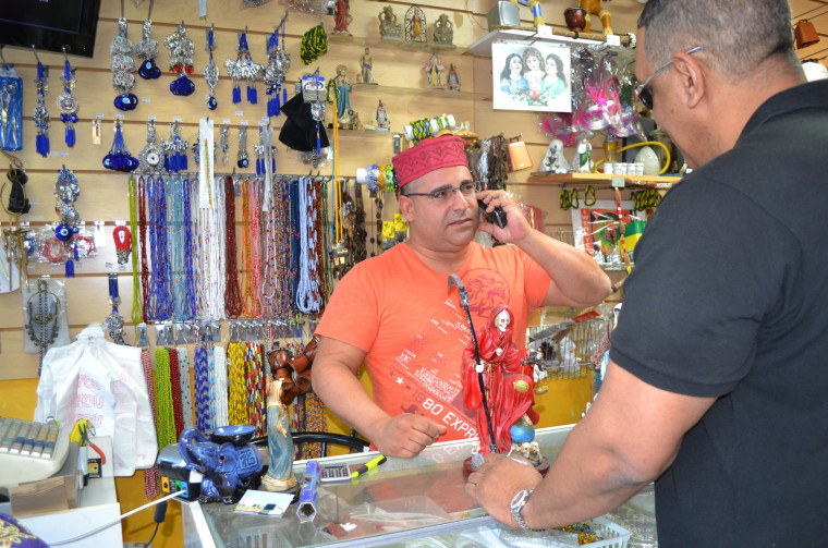 Image: Nelson Hernandez, owner of El Viejo Lazaro Botanica helping a customer