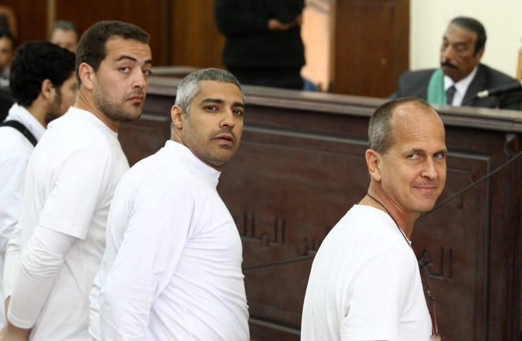 Image:  Australian journalist Peter Greste (R), Canadian-Egyptian journalist Mohammed Fahmy (C) and journalist Baher Mahmoud (L) standing in front of the judge's bench