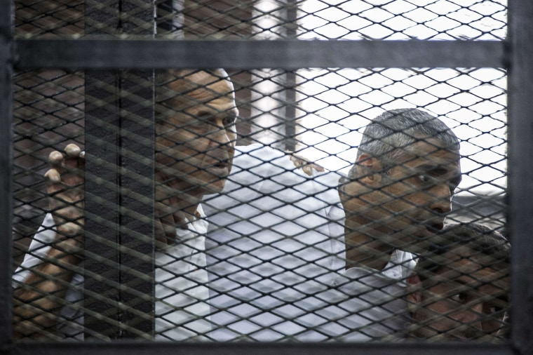 Image: Al-Jazeera's Peter Greste (L) and his colleagues, Mohamed Fadel Fahmy (C) and Baher Mohamed