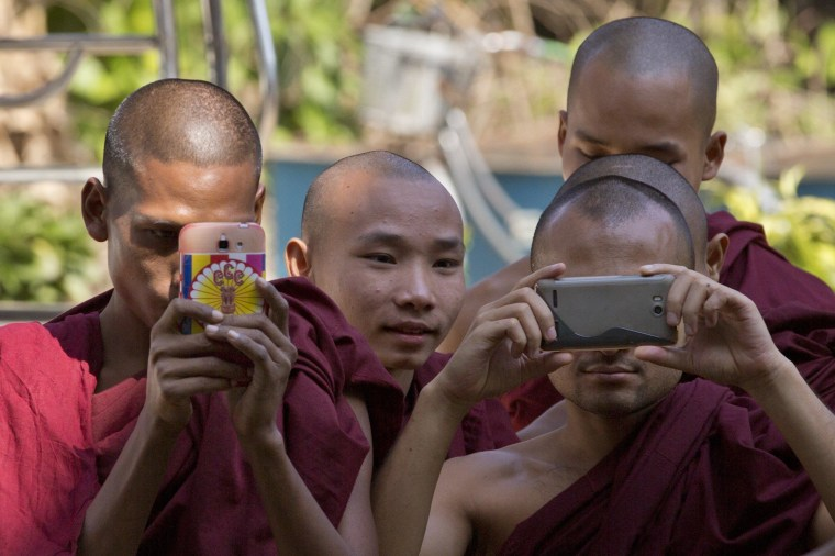 Image: Buddhist monks take pictures at a courthouse in Yangon, Myanmar