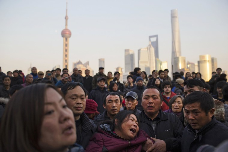 Image: A mother of a victim cries at the location where people were killed in a stampede incident during a New Year's celebration on the Bund in Shanghai
