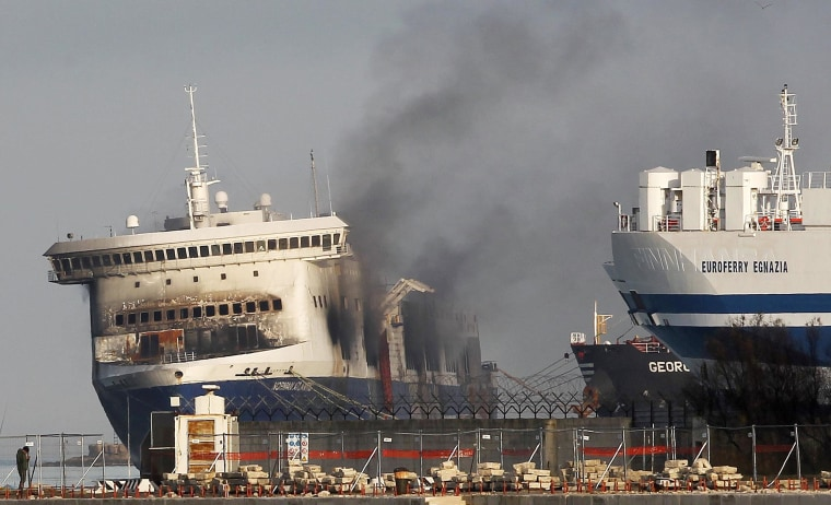 Image: Smoke rises from the Norman Atlantic multi-deck car-and-truck ferry docked at Brindisi harbor