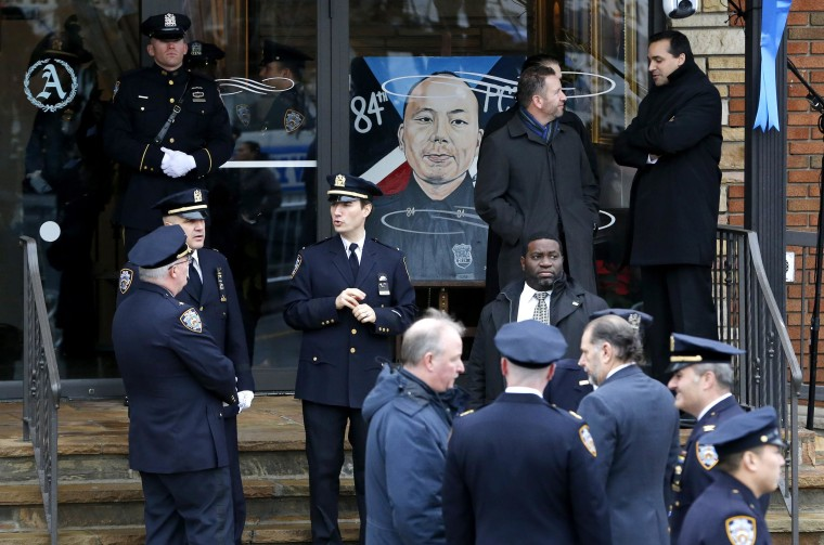 Image: A painting with the likeness of New York City police officer Wenjian Liu is displayed prior to funeral services for him at Aievoli Funeral Home