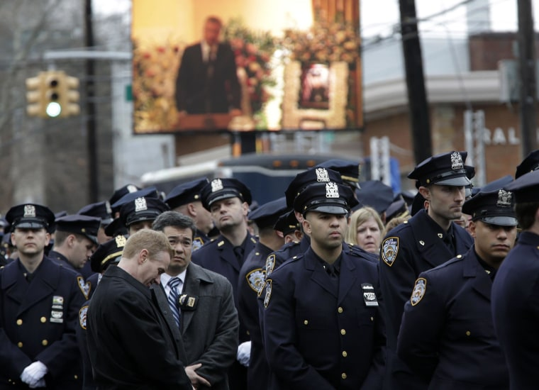 Image:  Some police officers turn their back to a large screen that displays New York City Mayor Bill de Blasio speaking during the funeral of Officer Wenjian Liu in Brooklyn