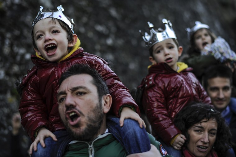 Image:  People enjoy the Cabalgata Los Reyes Magos (Cavalcade of the three kings) the day before Epiphany, in Pamplona, northern Spain, Monday, Jan. 5, 2015.
