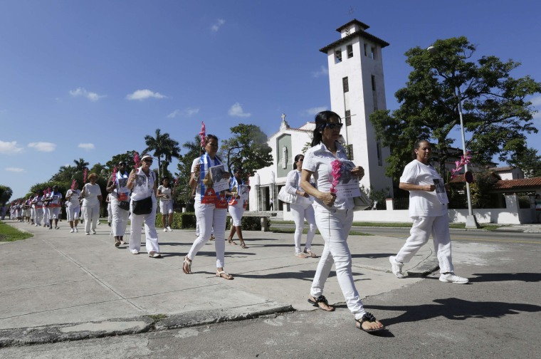 Image: The Ladies in White, an opposition group, hold flowers and pictures of their late leader Laura Pollan as they march during their weekly anti-government protest in Havana
