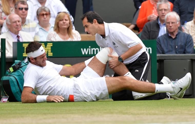 Image: Argentina's Juan Martin Del Potro recieves attention to his knee