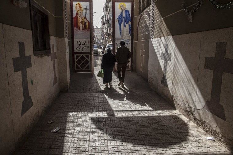 Image: Coptic Christians walk outside St. Markos Church in Minya, south of Cairo, Egypt, where two policemen guarding the church were shot dead