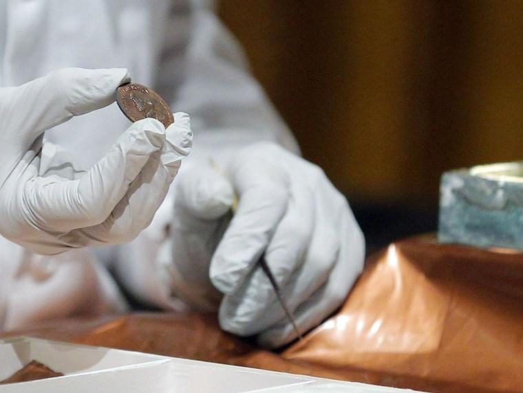Image: Conservator Hatchfield holds a copper medal