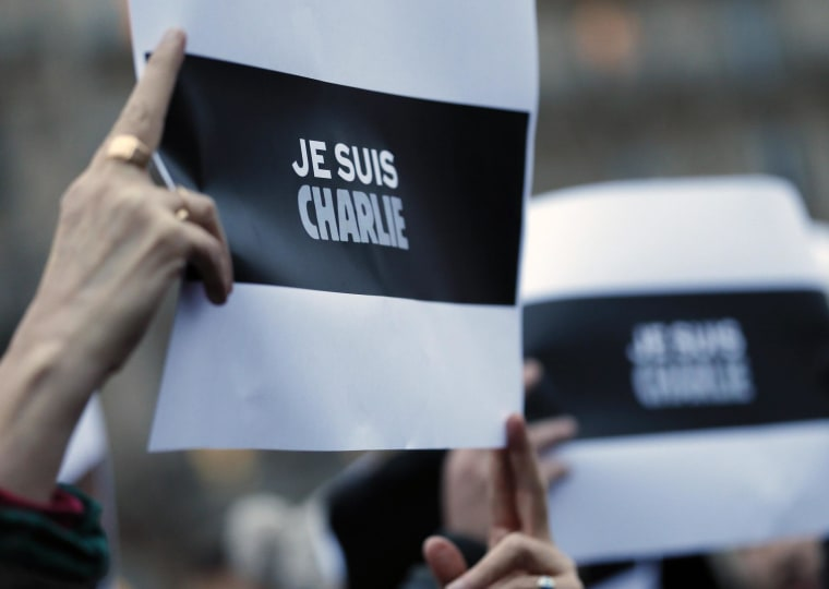 "Image: A person holds a placard which reads ""I am Charlie"" during a gathering at the Place de la Republique in Paris"