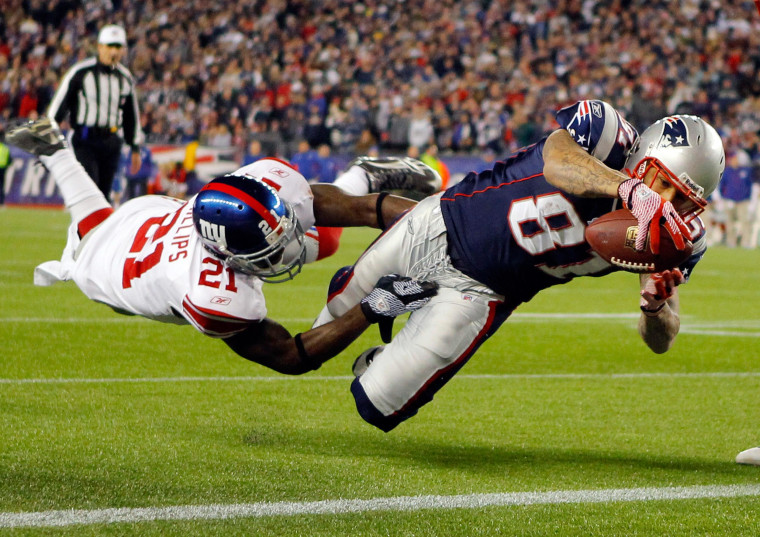 Image: New England Patriots Aaron Hernandez dives into the end zone for a touchdown through the arms of New York Giants Kenny Phillips in their NFL football game in Foxborough