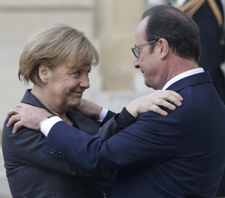 Image: French President Francois Hollande embraces German Chancellor Angela Merkel, left, as she arrives at the Elysee Palace, Paris, Sunday, Jan. 11, 2015