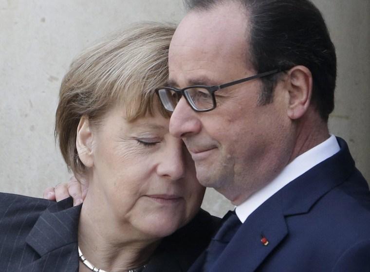 Image: French President Francois Hollande embraces German Chancellor Angela Merkel, left, as she arrives at the Elysee Palace, Paris, Sunday, Jan. 11