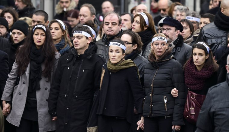 """Image: Cartoonist Corinne Rey (3rd left in green scarf) known as Coco, a survivor of the attack on the Charlie Hebdo satirical magazine, and other staff members, link arms as the take part in a Unity rally """"Marche Republicaine"""" on January 11, 2015 in Pari"""