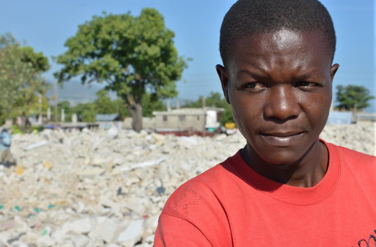 Image: Jean-Louis Wilner stands on the rubble of his demolished neighborhood in central Port-au-Prince, Haiti.