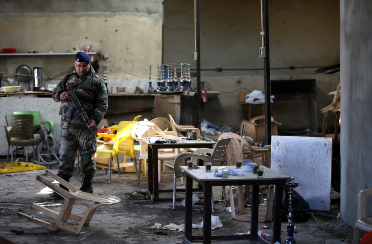 Image: A soldier walks inside a coffee shop that was damaged by a suicide bombing in Tripoli, Lebanon