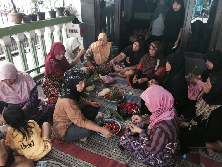 Image: Residents of Sawotratap, Indonesia, gather in the home of Agung Wahgu Darmono to weave funeral wreaths