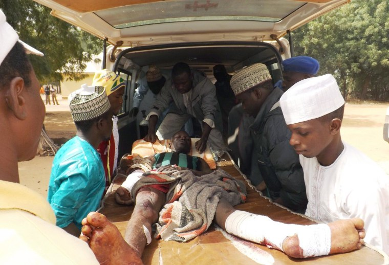 Image: A man injured in a suicide blast is transported by ambulancel in Potiskum, Nigeria, on Sunday