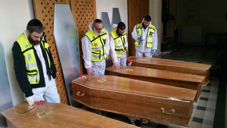 Image: Members of the Zaka emergency response team pray beside the coffins of four victims of an attack at a kosher supermarket on Friday, before their transport from Paris to Israel for burial, in Paris