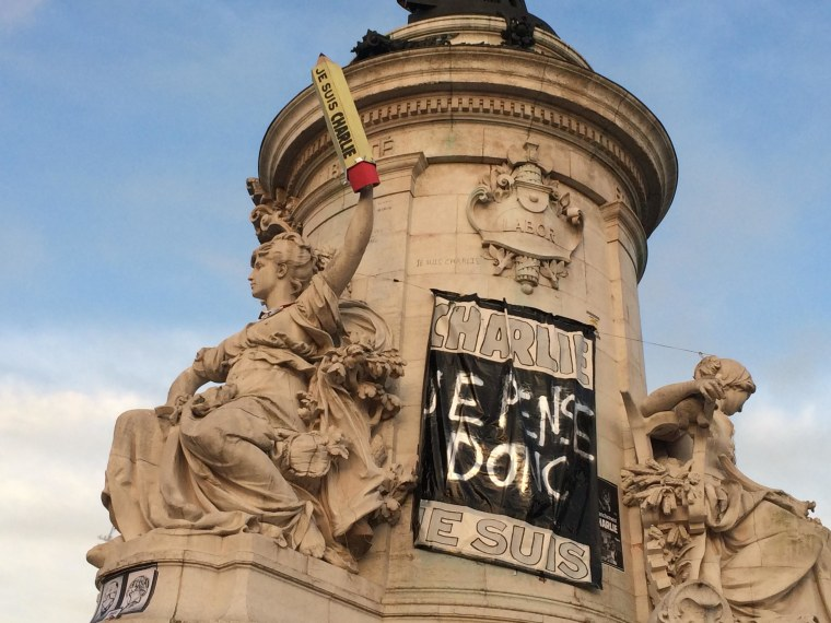 "The statue representing ""Liberty"" holds a pencil aloft bearing the ""I am Charlie"" motto at the Place de la Republique in Paris early on January 13. The plaza has been the centerpoint of rallies expressing solidarity with the victims of the massacre at the offices of the satirical newspaper Charlie Hebdo and pencils and pens have been used as a defiant symbol of support for freedom of speech."