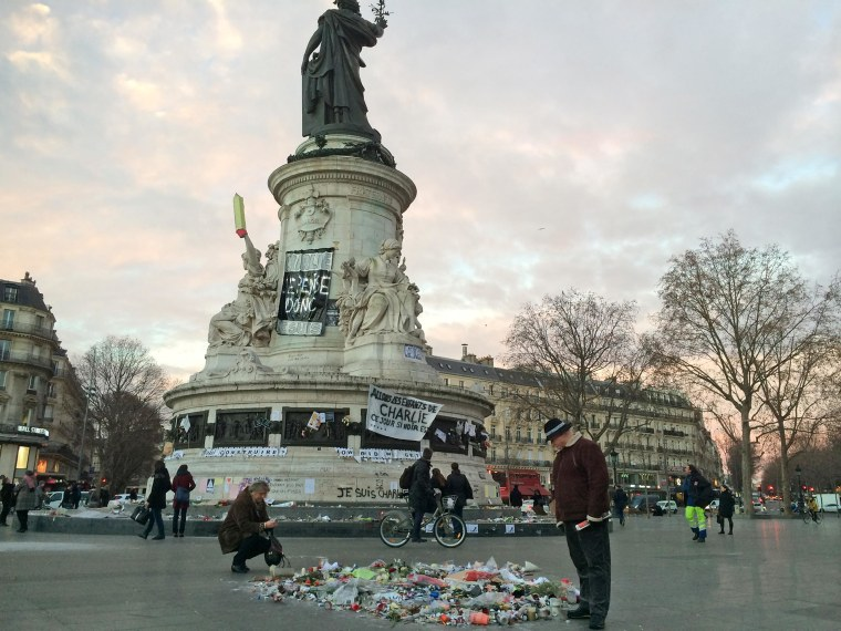 Tributes to the recent terrorist attacks adorn Place de la Republique early on Jan. 13 in Paris.