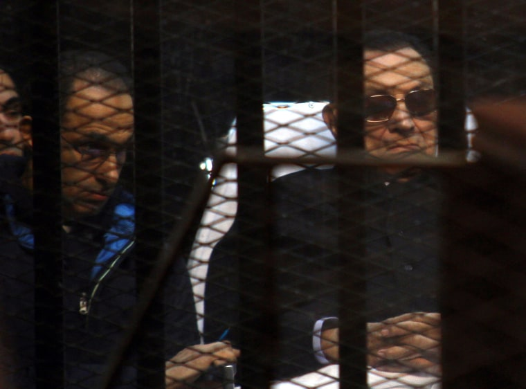 Image: A file picture of Egypt's former president Hosni Mubarak (R) and his son Gamal behind bars during a court hearing in in November