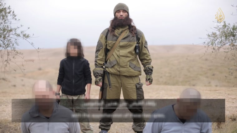 This frame grab image taken from a video released by ISIS a video on Tuesday appears to show a child soldier just before he shoots and kills two prisoners whom the militants accuse of spying for Russia.