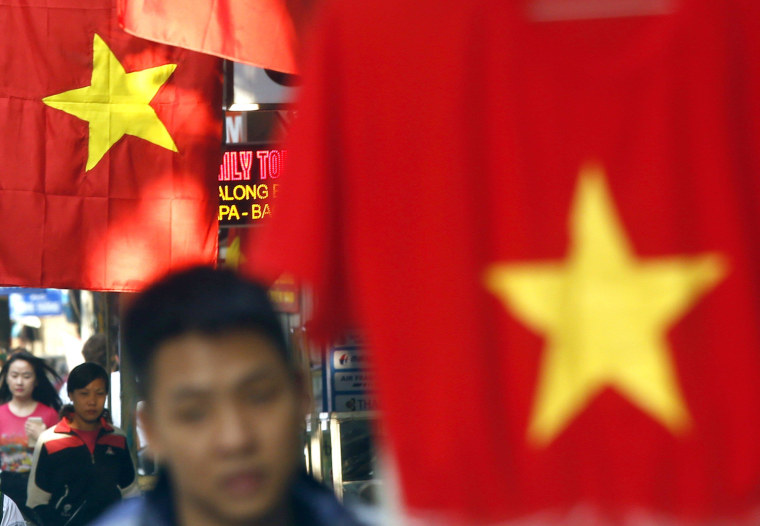 Image: Residents walk by national flags on a street in Hanoi