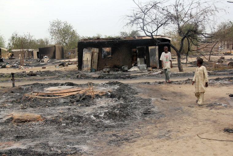 A file photo taken on April 21, 2013 shows children walking outside a charrred house in the remote northeast town of Baga, Borno State, after two days of clashes between officers of the Joint Task Force and members of the Islamist sect Boko Haram.